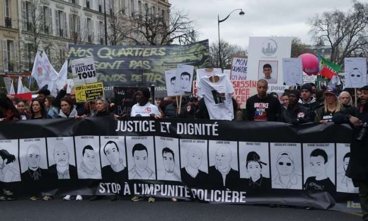 A photograph of the March for Dignity in Paris. Marchers are holding up a placard that reads 'Justice and Dignity' and 'Stop Police Violence'