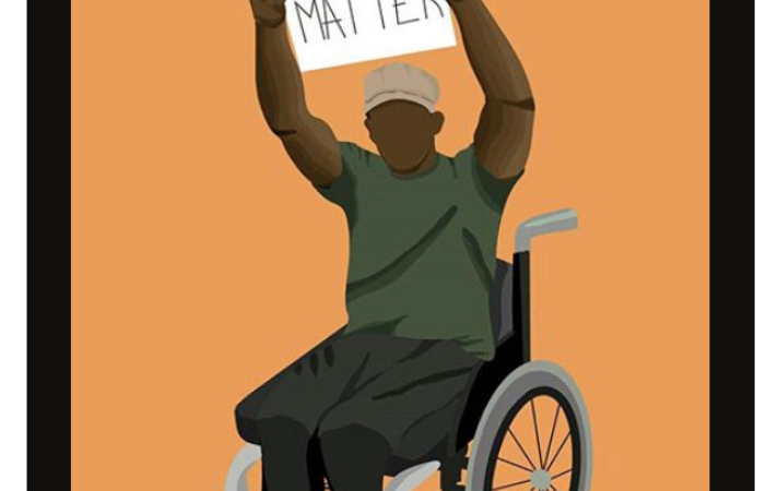 A Black man in a wheelchair holds a sign that reads Disabled Black Lives Matter