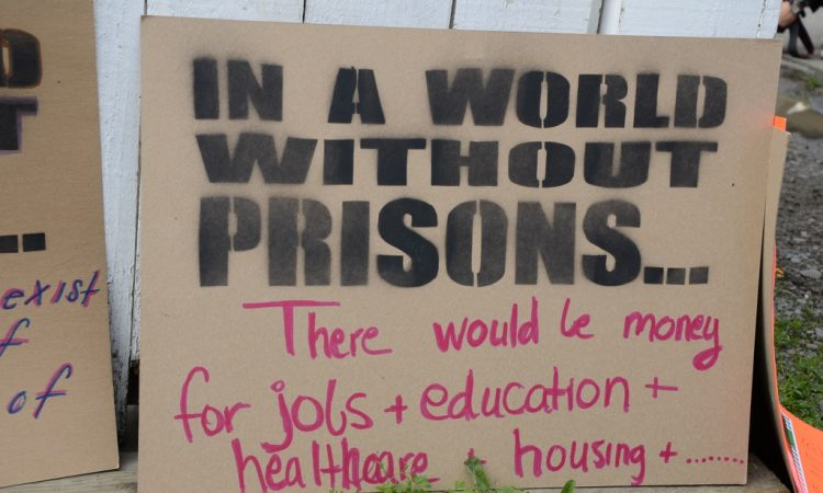 A photograph of a placard reading, 'In a world without prisons, there would be jobs and education and healthcare and housing